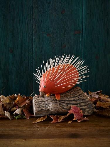 A hedgehog made from a pumpkin and toothpicks as Halloween decoration