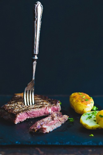 Sirloin steak with a fork and baked potatoes