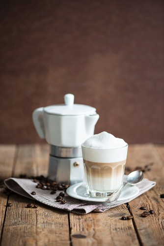 An espresso jug, a cappuccino and coffee beans