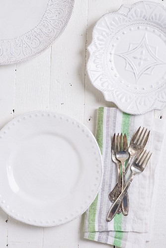 Three different white plates and silver cutlery on a fabric napkin