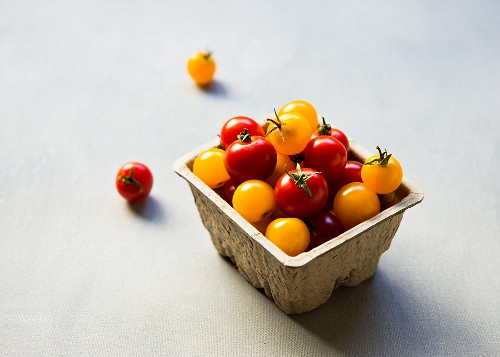 Red and yellow cherry tomatoes in a cardboard container