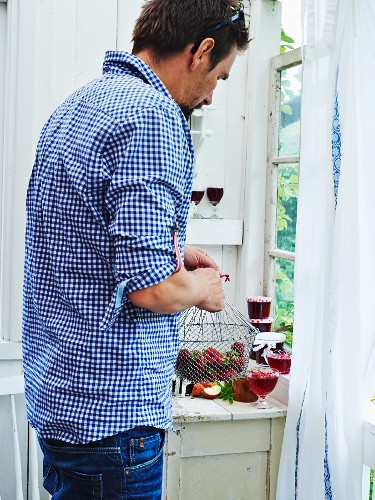 A man with glasses and jars of jam and strawberries in a vintage kitchen