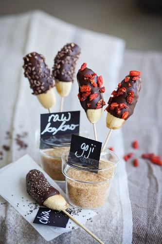 Mini bananas with a chocolate glaze, raw cocoa nibs, chia seeds and goji berries (superfood)