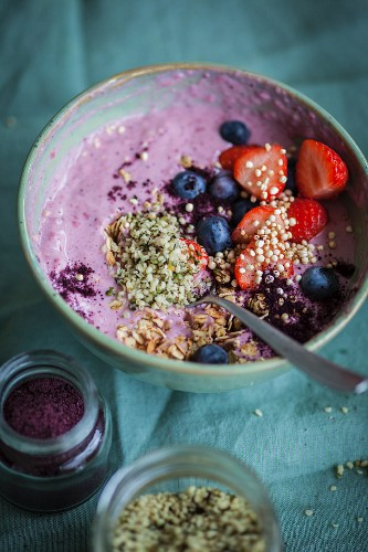 A superfood bowl with strawberries, blueberries, hemp and acai powder