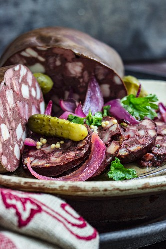 Sliced black pudding with gherkins and onions