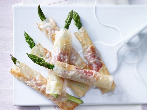 Green aspargus wrapped in crispy pastry with ham and cheese