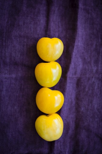 Four yellow tomatoes on a violet cloth