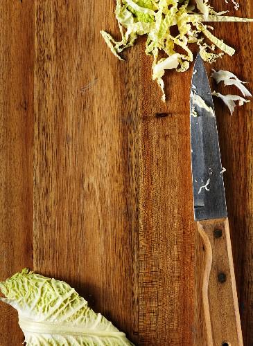 Wirsing, geschnitten, auf Holzuntergrund mit Messer