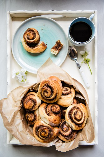Sweet yeast swirls with a brown sugar, cinnamon and pecan nut filling on a tray with coffee