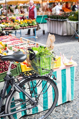 Fahrrad mit Einkäufen im Fahrradkorb auf einem Markt