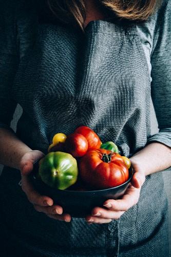Frau hält eine Schüssel mit verschiedenen Tomaten
