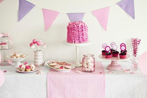 Kuchen und Gebäck in rosa Tönen auf einem Buffettisch