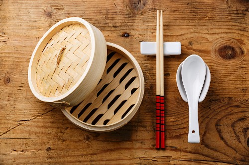 Asian kitchenware set Bamboo steamer, chopsticks and ceramic spoon on wooden background