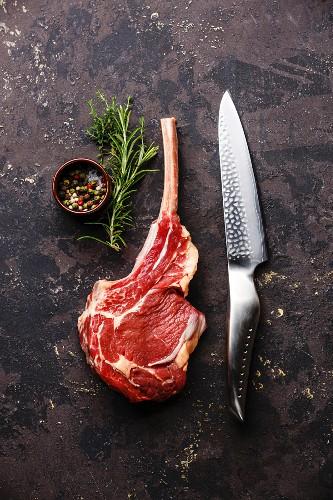 Raw fresh meat Veal rib Steak on bone and kitchen knife on dark background