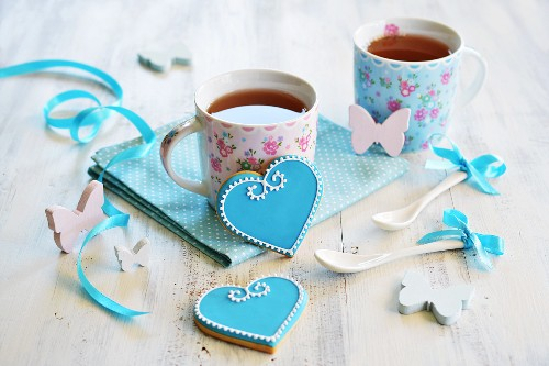 Heart-shaped biscuits decorated with blue and white icing and served with two cups of tea