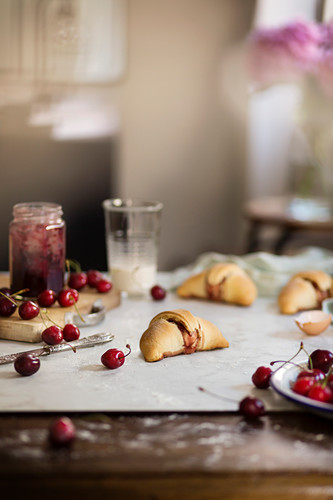 Homemade croissants with cherry jam on the table