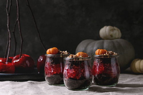 Layered Halloween dessert chocolate biscuit, raspberry jelly, nuts, marzipan pumpkin in glass jars and red caramel apples on branches
