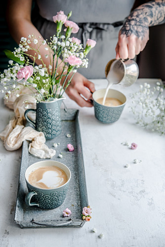 A woman pouring milk foam into a cup of coffee