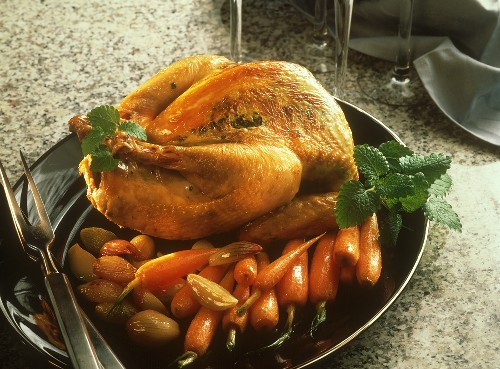 Guinea fowl stuffed with herbs under the skin, on carrots