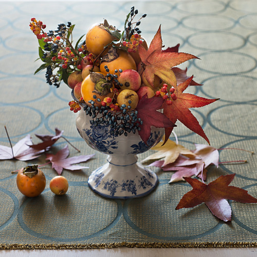 An autumnal arrangement of maple leaves, persimmon, ornamental apples and berry sprigs