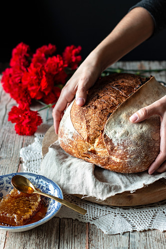 Unrecognizable person putting loaf of sourdough bread on rustic table near honeycomb and bouquet of red carnations