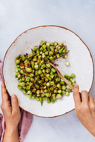 Stirring okra slices with spice mixture in a ceramic bowl