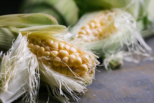 Top view of steps of fresh ripe corn peeling on black table