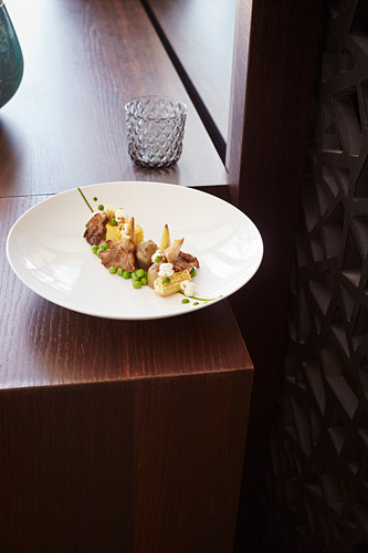 Fried oyster mushrooms with artichokes, polenta, peas and popcorn