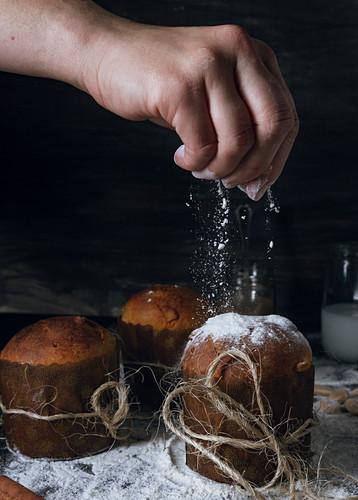 Crop person powdering icing sugar on fresh homemade Italian Christmas panettone
