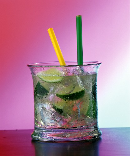 A glass of Caipirinha with yellow and green straws