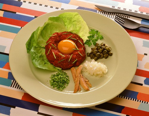 Steak tartare: minced beef with egg yolk, ingredients on plate