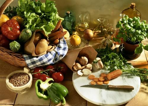 Still life with vegetable basket, mushrooms, herbs, oil & grain