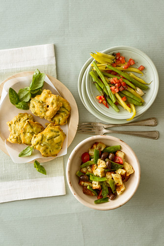 Green bean fritters, beans with tomatoes in parchment paper and a bean and bread salad
