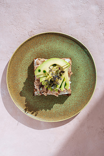 Tuna sandwich with slices of fresh avocado placed on plate