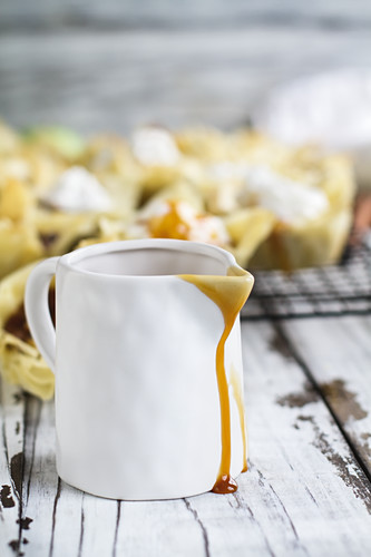 Sweet caramel sauce dripping from a white ceramic pitcher