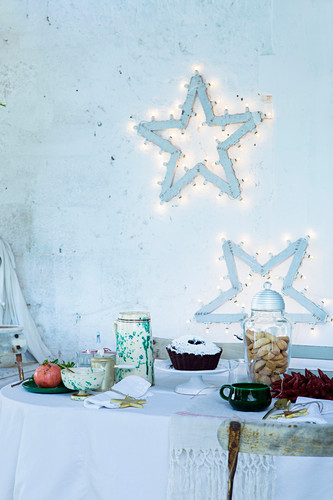 Festive fairy-light stars decorating wall above table set for afternoon coffee