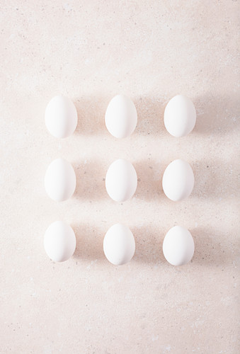 Nine white hen's eggs in rows on a light surface