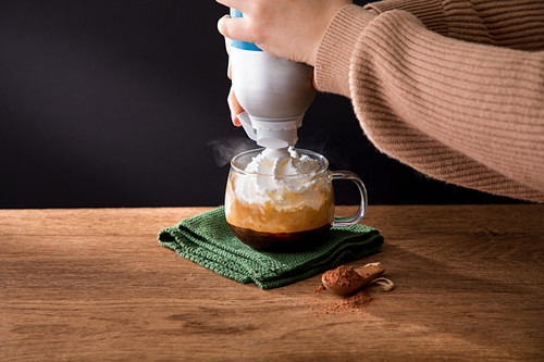 Preparing drink and pouring whipped cream into cup with hot black coffee with cinnamon