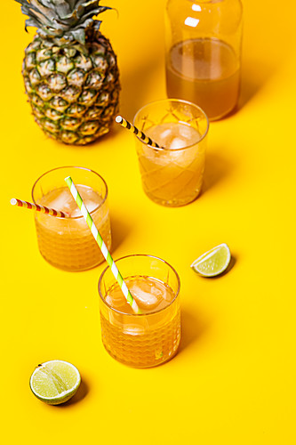 Iced tea with pineapple and coconut syrup in glasses on a yellow background
