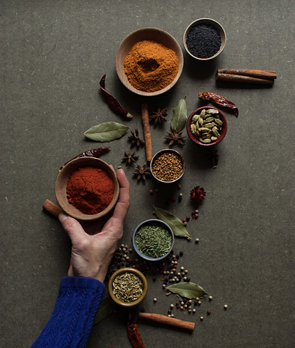hand holding pot with red paprika powder over gray table with set of assorted aromatic spices