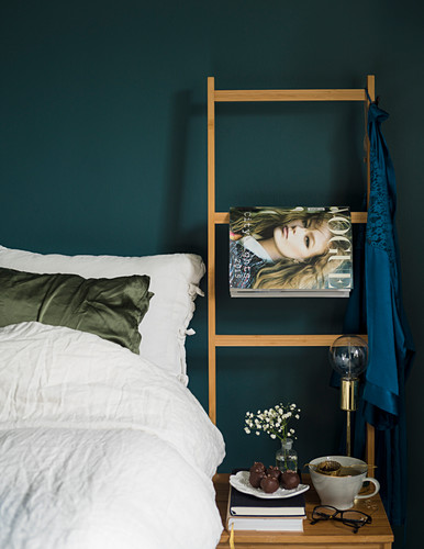 Bed with white bed linen and ladder used as magazine rack against petrol-blue wall