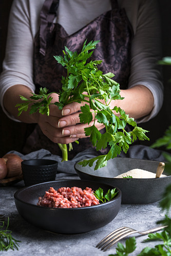 Unrecognizable female wearing apron keeping bunch of fresh parsley over bowl with raw minced meat