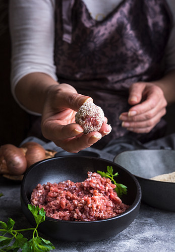 Unrecognizable person showing meatball over bowls with minced meat and bread crumbs during lunch preparation