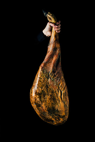 Crop unrecognizable person hand holding up a whole dry-cured ham leg on a black background