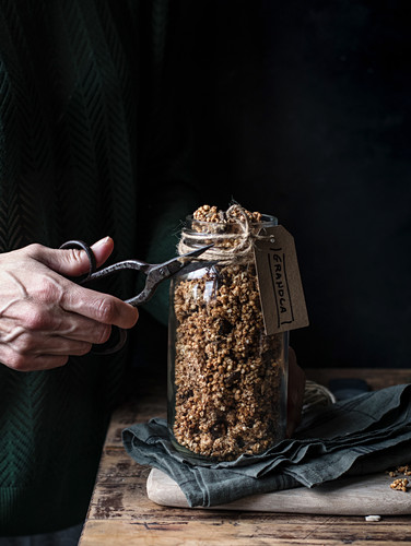 Unrecognizable person using retro scissor to cut rope with label from glass jar of millet and quinoa granola
