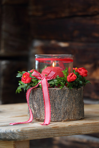 Candle lantern on stump decorated with handmade crepe flowers