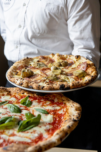 Pizza ready to be served, margherita and artichocke and culatello