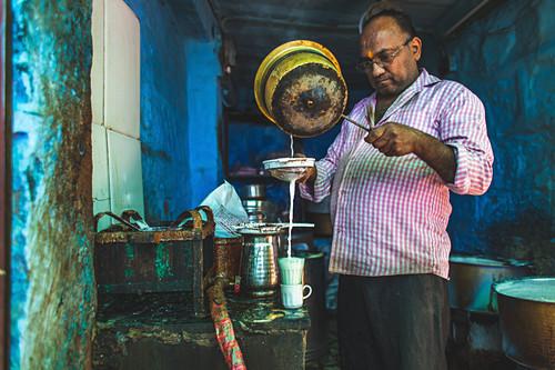 A man making a turmeric chai latte in a street kitchen (India)