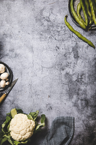 Organic green pods on round metal tray with mushrooms and cauliflower on grunge gray surface