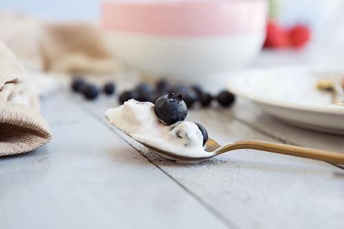 Vegan yoghurt with blueberries on a teaspoon